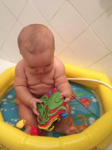 Tomando banho na piscininha brincando com o livrinho de plástico do polvo